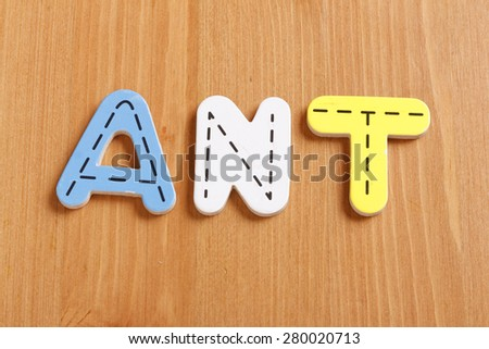 ANT, spell by woody puzzle letters with woody background - stock photo