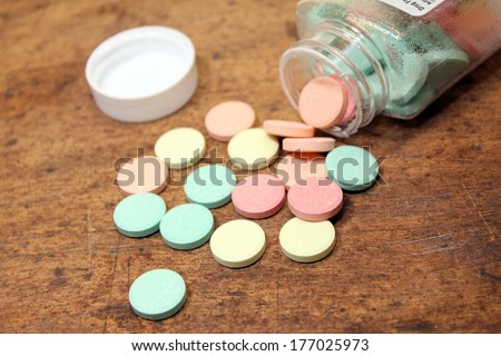 antacid bottle spilled out over wood background - stock photo