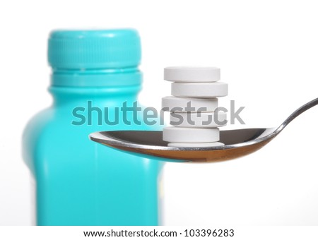 Antacid tablets on a spoon, a bottle of antacid blurred in the background - stock photo