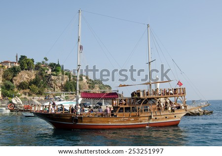 ANTALYA, TURKEY - AUGUST 18, 2014:  A ship with decorative masts and other fittings taking tourists around the coastline of Turkey.  Antalya harbour. - stock photo