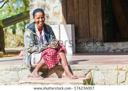 ANTANANARIVO, MADAGASCAR - JULY 2, 2011: Unidentified Madagascar woman smiles on a porch of a house. People in Madagascar suffer of poverty due to slow development of the country - stock photo