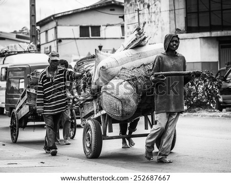 ANTANANARIVO, MADAGASCAR - JUNE 28, 2011: Unidentified Madagascar man carriage with different stuff. People in Madagascar suffer of poverty due to the slow development of the country - stock photo