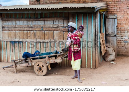 ANTANANARIVO, MADAGASCAR - JUNE 29, 2011: Unidentified Madagascar man carries her little baby on his back. People in Madagascar suffer of poverty due to the slow development of the country - stock photo