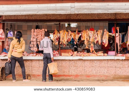 ANTANANARIVO, MADAGASCAR - JUNE 29, 2011: Unidentified Madagascar man chooses meat and sausages at the market. People in Madagascar suffer of poverty due to the slow development of the country - stock photo