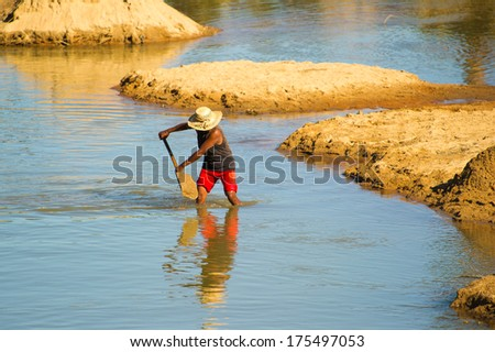 ANTANANARIVO, MADAGASCAR - JUNE 29, 2011: Unidentified Madagascar man digs the sand from the bottom of the river. People in Madagascar suffer of poverty due to the slow development of the country - stock photo