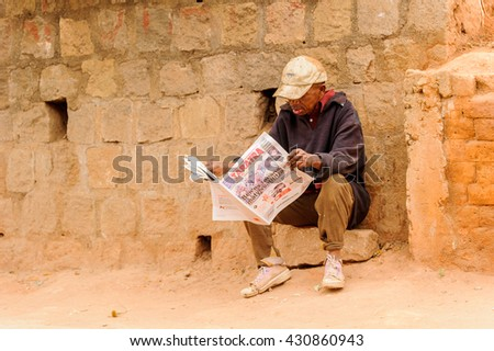 ANTANANARIVO, MADAGASCAR - JUNE 28, 2011: Unidentified Madagascar man reads a Taratra newspaper sitting on a stone. People in Madagascar suffer of poverty due to the slow development of the country - stock photo