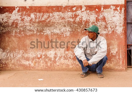 ANTANANARIVO, MADAGASCAR - JUNE 29, 2011: Unidentified Madagascar man sits near an old wall. People in Madagascar suffer of poverty due to the slow development of the country - stock photo