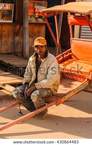 ANTANANARIVO, MADAGASCAR - JUNE 29, 2011: Unidentified Madagascar man sits on a carriage. People in Madagascar suffer of poverty due to the slow development of the country - stock photo
