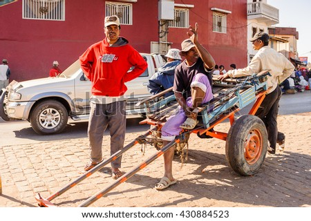 ANTANANARIVO, MADAGASCAR - JUNE 27, 2011: Unidentified Madagascar man sitting on the carriage in the street. People in Madagascar suffer of poverty due to the slow development of the country - stock photo
