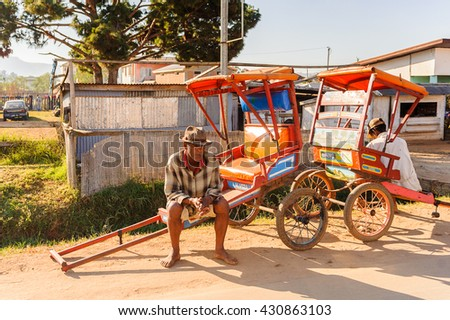 ANTANANARIVO, MADAGASCAR - JUNE 29, 2011: Unidentified Madagascar old man sits on a carriage. People in Madagascar suffer of poverty due to the slow development of the country - stock photo