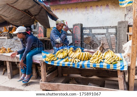 ANTANANARIVO, MADAGASCAR - JUNE 30, 2011: Unidentified Madagascar woman sells bananas at the market. People in Madagascar suffer of poverty due to slow development of the country - stock photo