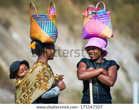 ANTANANARIVO, MADAGASCAR - JUNE 27, 2011: Unidentified Madagascar women walk and carry bags on their heads and a baby on a back.People in Madagascar suffer of poverty due to development of the country - stock photo