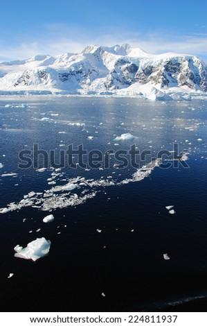 antarctic ice floe in blue sea - stock photo