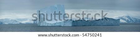 Antarctic ice island in ocean - stock photo