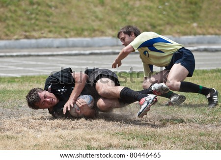 ANTARES - ARGO, UKRAINE, KIEV - JUNE 12 : Rugby players in action at a Ukrainian National Championship rugby match, Antares(in black) vs. Argo(in yellow), June 12, 2011 in Kiev, Ukraine. - stock photo