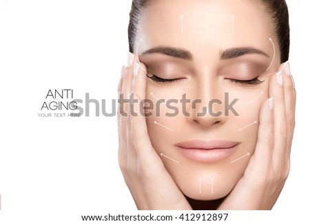 Anti aging treatment and plastic surgery concept. Beautiful young woman with hands on cheeks and eyes closed with a serene expression and white arrows over face. Isolated on white with copy space - stock photo