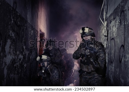 Anti-terrorist operation. Soldiers in full gear. Going up in smoke. Destroyed object. - stock photo