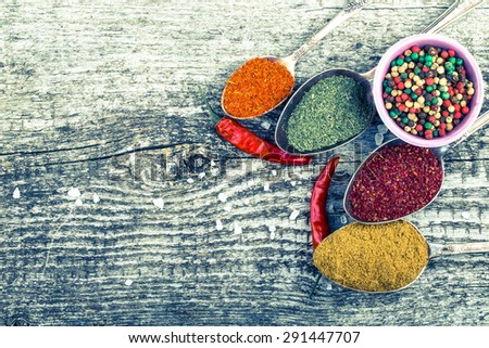 Antic metal spoons and small bowl with different kinds of spices on old wooden board. Selective focus. Toned. - stock photo