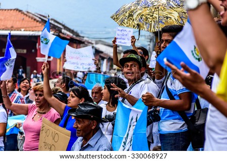Antigua, Guatemala - August 27, 2015: Locals waving Guatemalan flags & slogans protesting against government corruption & demanding resignation of President Otto Perez Molina in front of city hall. - stock photo
