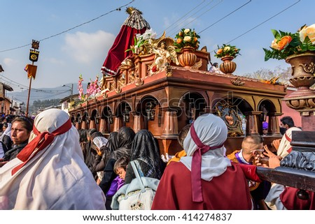 Antigua, Guatemala -  March 24, 2016: Local men & women take part in Holy Thursday procession with float of Virgin Mary in colonial town with most famous Holy Week celebrations in Latin America. - stock photo