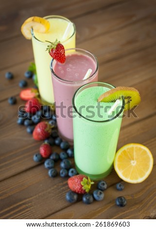 Antioxidant. Fresh milk, strawberry, blueberry and banana drinks on wodeen table, assorted protein cocktails with fresh fruits. - stock photo