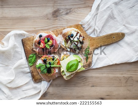Antipasti brusquetta set on a rustic wooden board over a linen kitchen towel and wooden background - stock photo