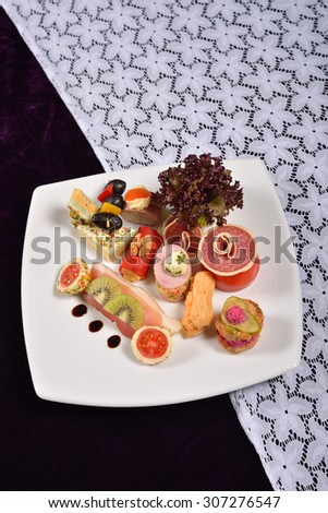 Antipasto and catering platter with different appetizers (fruits, vegetables, meats, cheeses), restaurant menu - stock photo