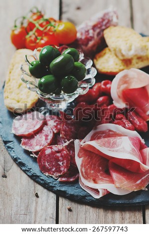 Antipasto with ham, olive and tomato on the wooden table, selective focus and toned images - stock photo