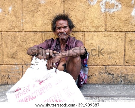 ANTIPOLO CITY, PHILIPPINES - MARCH 15, 2016: An old man rests at a sidewalk in a street in Antipolo City in the province of Rizal, Philippines - stock photo