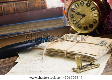 antique alarm clock with pile of books and mail  - stock photo