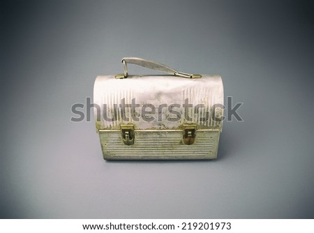 Antique aluminum lunch box against gray background. Analog filter.  - stock photo