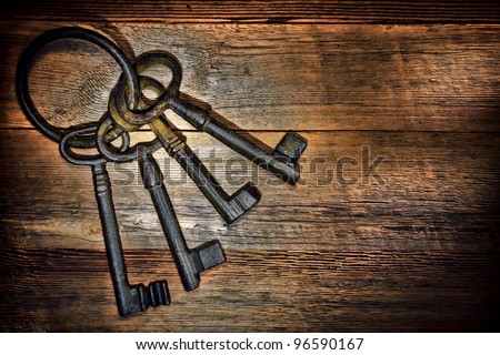 Antique and rusty medieval castle skeleton door keys with old corroded metal ring on antique weathered barn wood board planks - stock photo