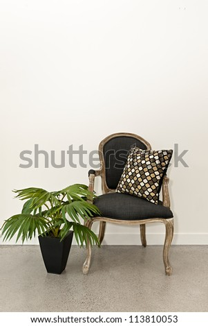 Antique armchair furniture with houseplant against white wall - stock photo