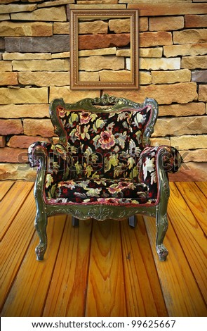 Antique armchair in the brick wall room with a frame hanging on. - stock photo