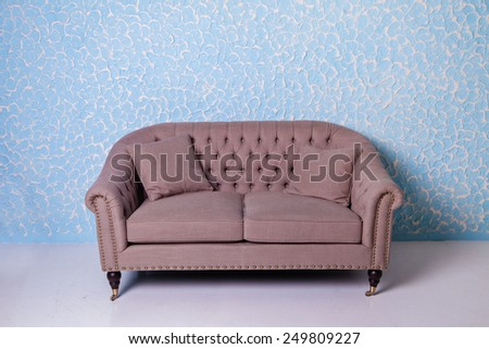 Antique armchair sofa couch in vintage room on blue textured wall - stock photo