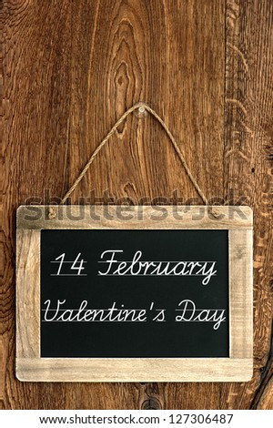 antique blackboard on wooden wall with sample text 14 February Valentine's Day. vintage background - stock photo
