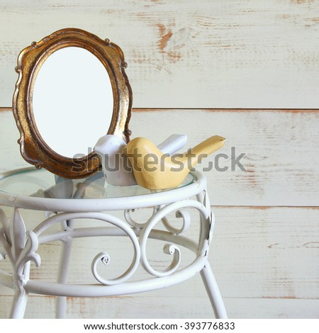 Antique blank vintage style frame and couple of wood decor birds on vintage table.  template, ready to put photography - stock photo
