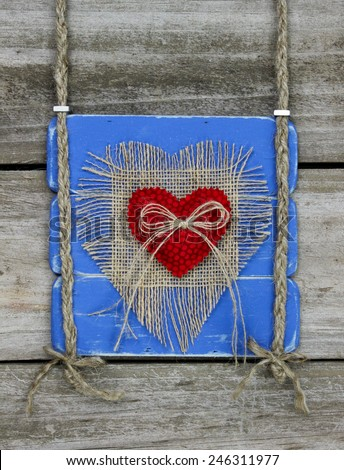 Antique blue rustic wood sign with red fabric and burlap hearts hanging by braided rope on distressed wooden door - stock photo