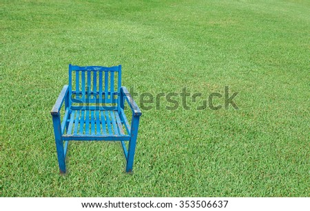 Antique blue wooden chair on green grass background  - stock photo