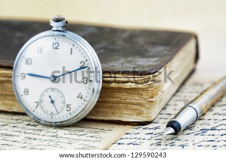 Antique book and clock - stock photo