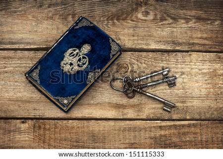 antique book and old keys over rustic wooden background. grunge vintage backdrop - stock photo