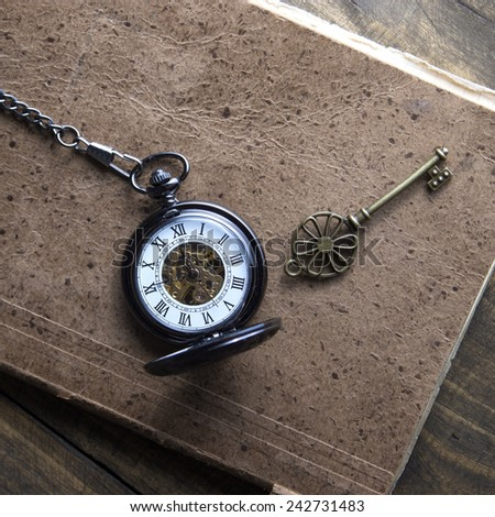 Antique book and pocket watch on grunge wooden table, from above - stock photo