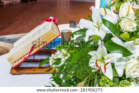 Antique Book on the altar for the celebration of Holy Mass in a Catholic Italian church with white flowers and green leaves as ornament - stock photo
