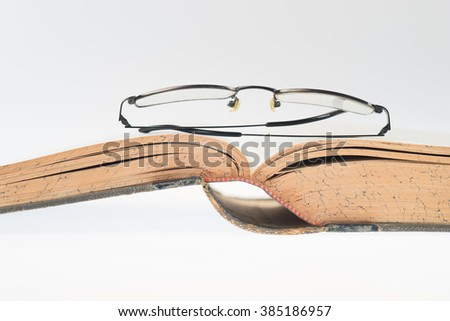 antique book with glasses, selective focus - stock photo
