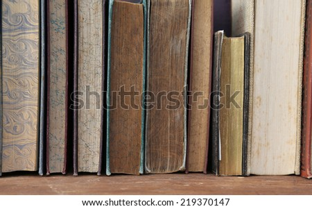 antique books on wooden shelf. - stock photo