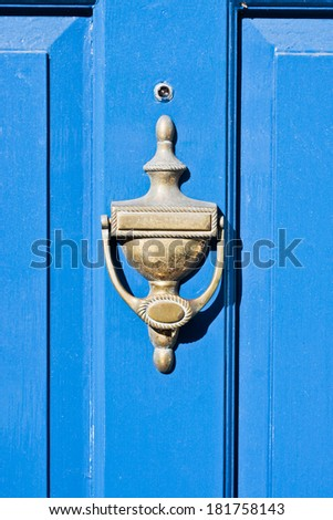 Antique brass door knocker on a blue door - stock photo