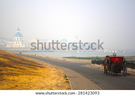 antique carriage rides with the old Russian city - stock photo