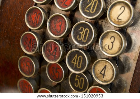 Antique Cash Register Buttons / A detail of a vintage dirty cash register with currency in dollars - stock photo