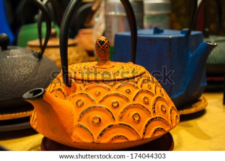 antique cast iron tea pot yellow - stock photo