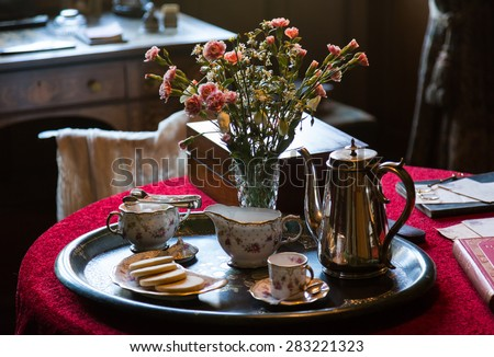 Antique china tea cup and pot on silver tray with flowers on red tablecloth in old drawing room - stock photo